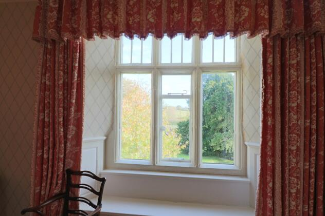 Feature stone-mullioned window and window seat in Yate room with countryside views